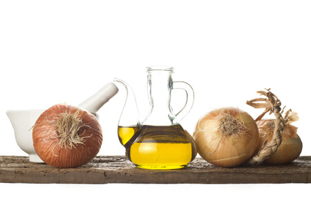 Olive oil, onions and mortar on a wooden shelf isolated on white background photo