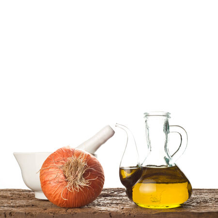 Olive oil, onion and mortar on a old wooden shelf isolated on white background photo