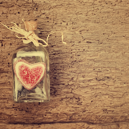 space for writing: Valentines day card, bottle and gummy heart on vintage wooden background with space for writing message or put photos Stock Photo