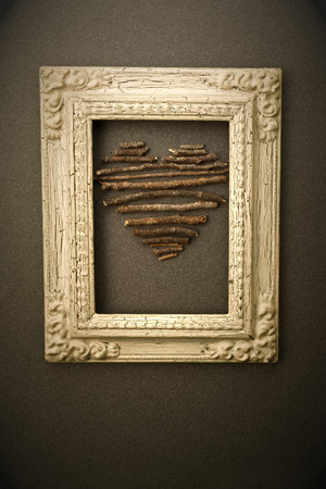 st  valentin: Postcard valentines day, heart made with wooden sticks inside an old picture hanging on the wall