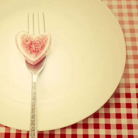 st valentin: Greeting card valentines day, gummy heart on a fork on a plate retro style