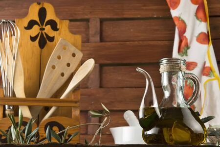 extra virgin olive oil: Glass bottle with extra virgin olive oil and kitchen utensils on wooden rustic kitchen