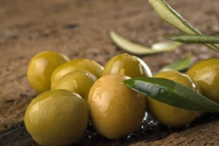 rustic food: Olives marinated with olive oil on an old wooden table, closeup photo