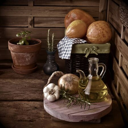 Extra virgin olive oil, garlic, squash, rosemary and onion in an old country kitchen photo