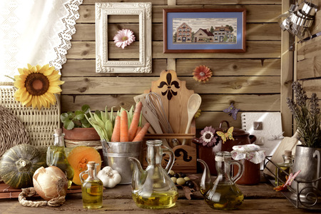 extra virgin olive oil: Extra virgin olive oil, vegetables and cooking utensils in rustic kitchen Stock Photo