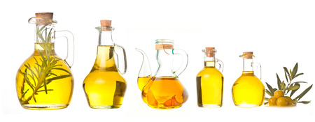 Extra virgin olive oil cruets and flavored olive oils with rosemary and garlic Archivio Fotografico