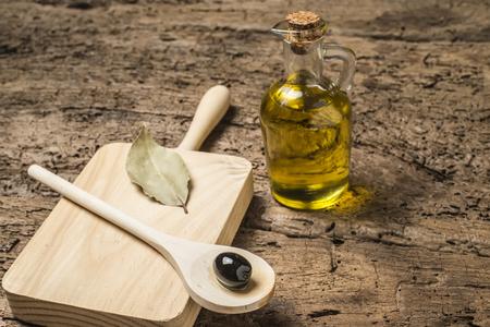 aceite de cocina: Cuchara de madera con negro de oliva en una botella tabla de cortar y vaso de aceite de oliva en el fondo de madera vieja Foto de archivo