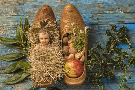 clogs: Christmas time, antique figurine of Baby Jesus and offerings in traditional farmer clogs, on rustic background