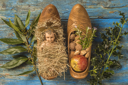 baby jesus: Christmas time, antique figurine of Baby Jesus and offerings in traditional farmer clogs, on rustic background
