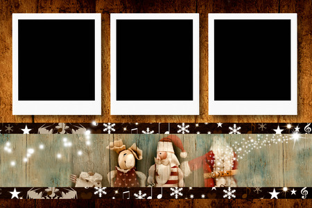 photo album: Christmas postcards, three empty photo frames and vintage Santa dolls on wooden background