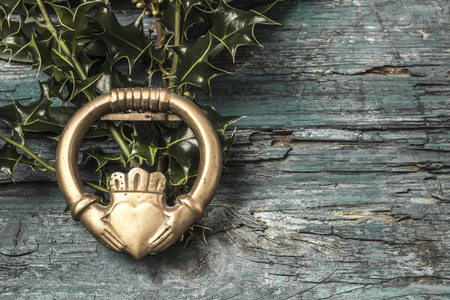 Claddagh and holly branches  irish symbol of love, friendship and loyalty in old wooden background Stock Photo