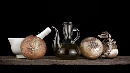sauce bottle: Olive oil, onions and mortar  on a old wooden shelf isolated on black  background Stock Photo