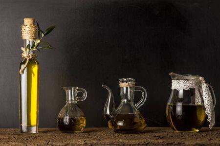 extra virgin olive oil: Bottle and glass jars of extra virgin olive oil on rustic background