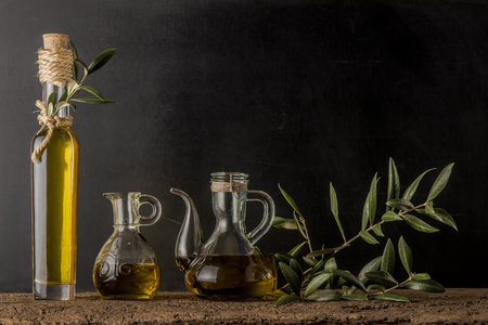 Bottle and glass jars of extra virgin olive oil on rustic background