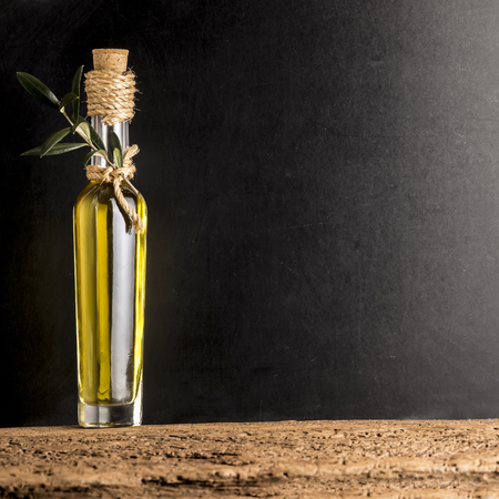 extra virgin olive oil: Extra virgin olive oil in rustic glass bottle on rustic background