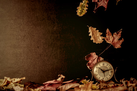 back in an hour: Old alarm clock and autumn leaves, blackboard background with copy space