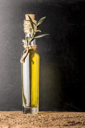 extra virgin olive oil: Extra virgin olive oil in rustic glass bottle on dark background, vertical image