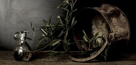 greek pot: L'olio d'oliva e vecchia pentola di rame e foglie di ulivo su sfondo scuro Archivio Fotografico