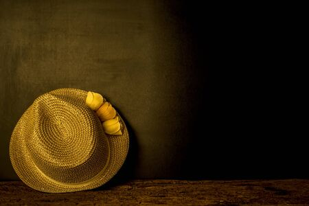 Girl straw hat on wooden table and blackboard wall goldtone with copy space Stock Photo