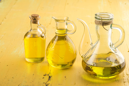 extra virgin olive oil: Three oilers glass of extra virgin olive oil on yellow wooden table