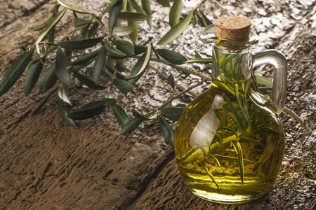 extra virgin olive oil: Extra virgin olive oil flavored with rosemary on old wood Stock Photo