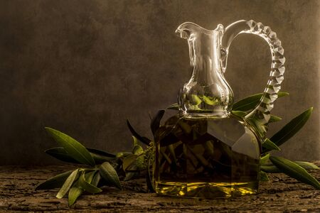 space for writing: Virgin olive oil in luxurious old oil jar and an olive branch in an ocher background with empty space for writing text Stock Photo