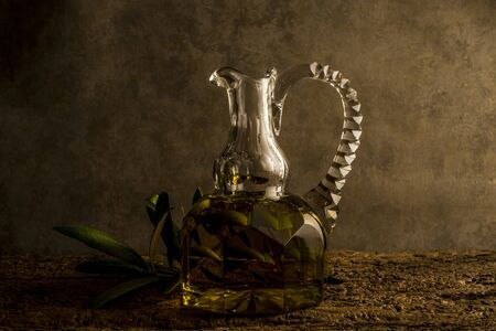 cruet: Virgin olive oil in luxurious old oil jar and an olive branch in an ocher background with empty space for writing text oil glass cruet and an olive branch in an ocher background