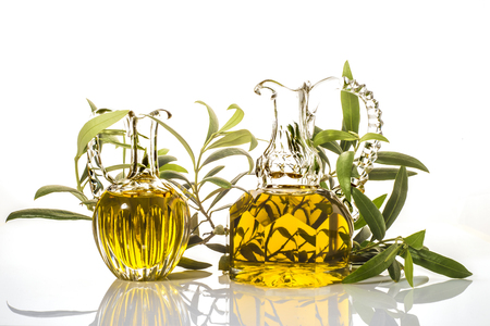 Extra virgin olive oil, two old glass jars and olive branches isolated on white background