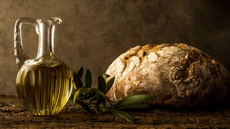 Virgin olive oil in vintage glass oil jar and rustic bread in an ocher background with empty space for message Stock Photo