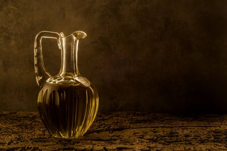 cruet: Extra virgin olive oil in vintage elegant oil cruet on old table in an ocher background with empty space for message