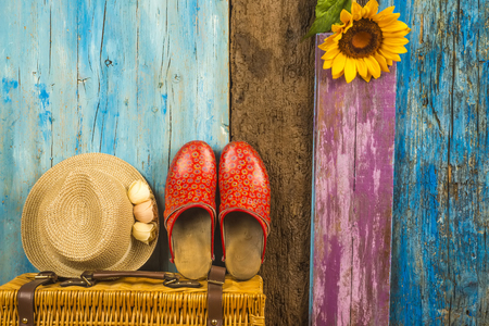 Summer background, suitcase, straw hat and clogs girl in multicolored wooden background with space to write text