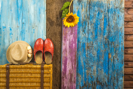 Summer travel background, suitcase, straw hat and clogs girl in multicolored wooden background with space to write text Stock Photo