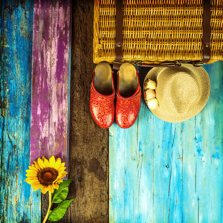 Summer travel background, suitcase, straw hat, sunflower and clogs girl in multicolored wooden background with space to write text Stock Photo
