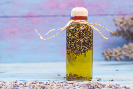 flavored: Lavender oil, olive oil flavored  in bottle with seeds and lavender flowers on wooden table