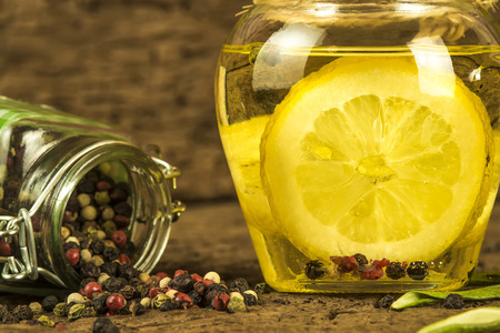 flavored: Olive oil flavored with lemon and  peppercorns in  glass bottle on old wooden background