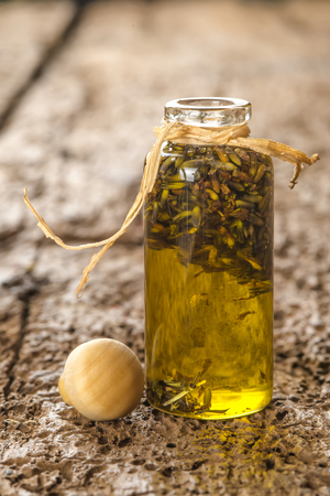 infused: Lavender seeds macerated in olive oil in a small glass jar on rustic wooden table