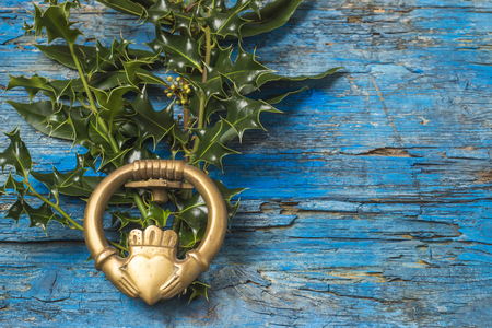Claddagh and holly branches irish symbol of love, friendship and loyalty in old wooden background
