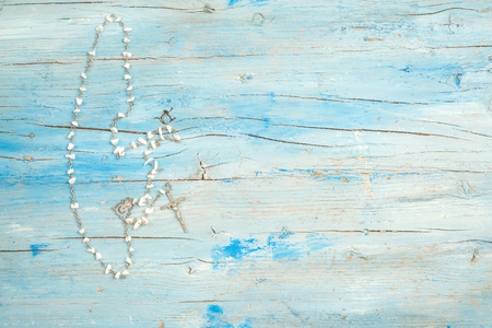 space for writing: Christian rosary on blue rustic wood with space for writing text Stock Photo