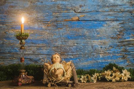 carte de Noël, Jésus bébé dans son berceau et bougie cru en arrière-plan en bois rustique avec copie espace Banque d'images