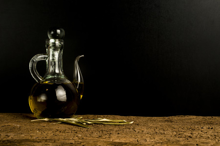 cruet: Olive oil, extra virgin olive oil vintage cruet on old wooden table with dark blank space for message