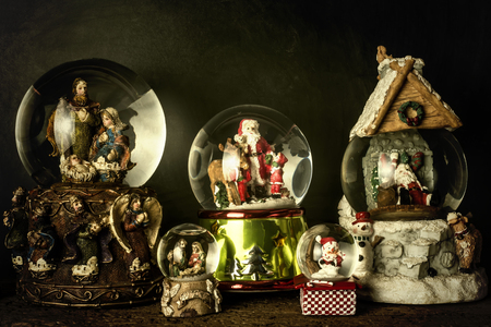 Christmas vintage card, snowflakes crystal globes with christmas figurines on rustic background Stock Photo