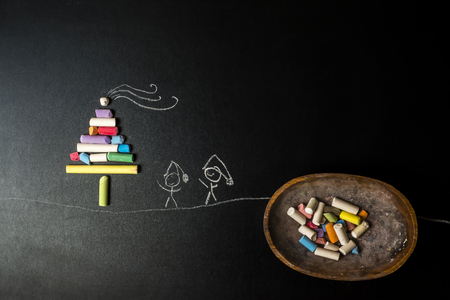 chalks: Funny Christmas Greeting Card, tree made with chalks and stickman children drawing in a blackboard with copy space for message