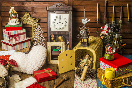 o'clock: Figurine of the Jesus child surrounded by Christmas objects, gifts, decoration, antiques and clock marking twelve oclock