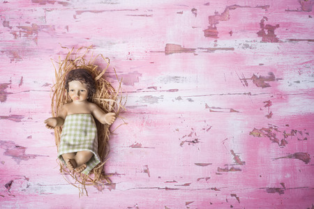 Baby Jesus Christmas background, cute figurine of Baby Jesus in his crib on rustic pink wooden background with blank space.