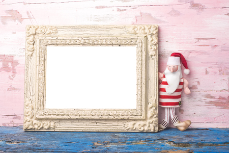 rag doll: Christmas Santa card, Santa Claus rag doll and empty vintage photo frame on pink wooden background