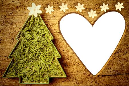 Cute Christmas tree with flower on old wooden background with empty frame heart shaped