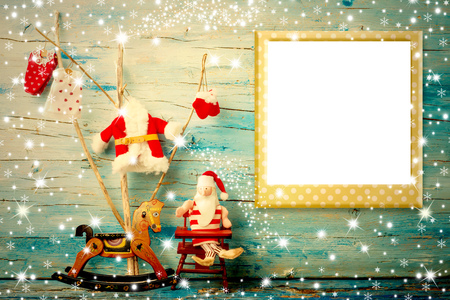 Christmas photo frame card, Santa Claus rag doll, cute tree and rocking horse with empty photo frame, vintage tone wooden background