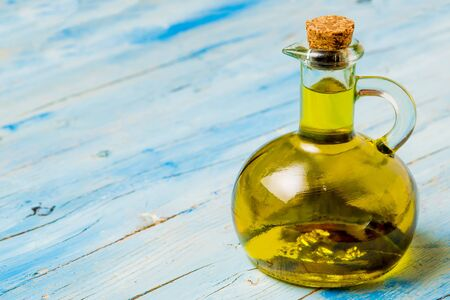 Extra virgin olive oil in glass jar on blue wooden table