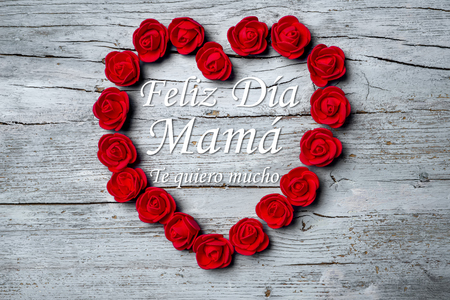 heart very: Happy Mothers Day,  Feliz día mama Happy day mom in spanish language and Te quiero mucho I love you very much in spanis language, from above shot of red roses arranged in shape of heart wishing . Stock Photo