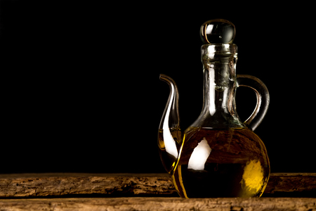 Extra virgin olive oil, old oil glass on a wooden table on black background Stock Photo